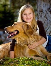 Young girl hugs her Golden Labrador